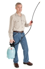 A pest controller spraying chemicals outside a house.