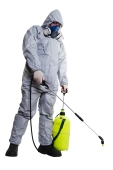 A pest controller in protective clothes spraying chemicals under a roof.